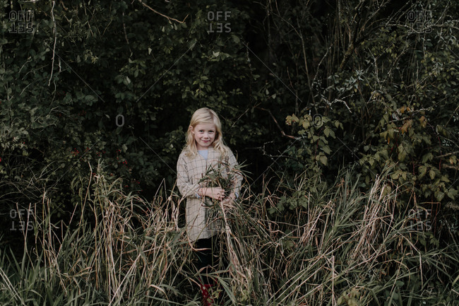 Portrait of young blonde girl standing at the edge of a forest