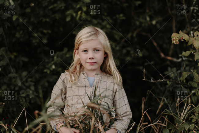 Portrait of young girl standing at the edge of a forest