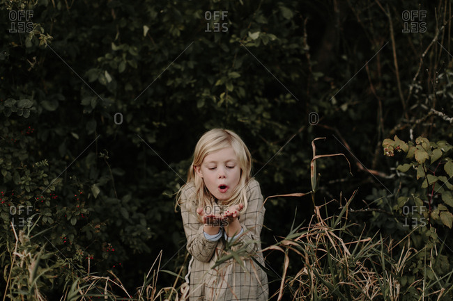 Young girl standing at the edge of a forest blowing berries from her hands