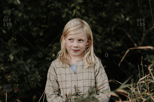 Portrait of blonde girl standing at the edge of a forest