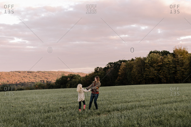 Mom and daughter dancing together in a field