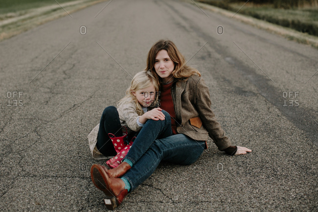 Mom embracing her daughter on country road