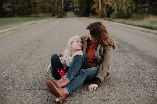 Mother and her daughter sitting together on country road