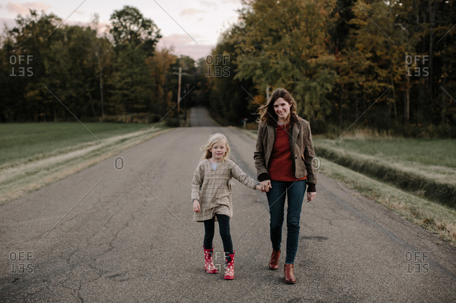 Mom and daughter walking hand in hand on country road