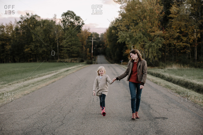 Mother and daughter walking hand in hand on country road