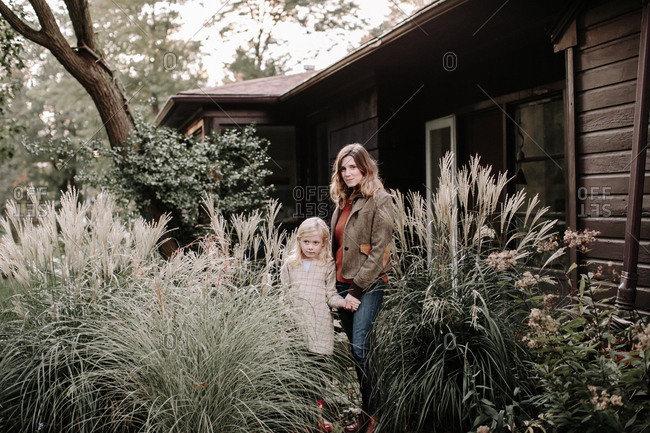 Mother and daughter standing by large plants in front of house