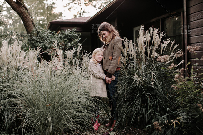 Daughter hugging mom while standing by large plants in front of house