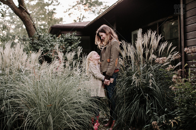 Daughter looking up at mom while standing by large plants in front of house