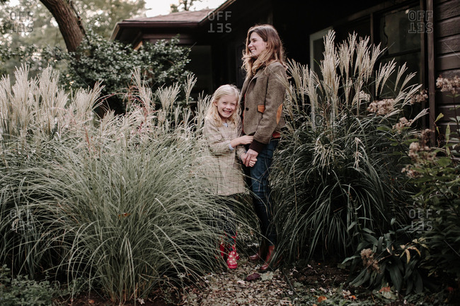 Daughter and mother laughing while standing by large plants in front of house