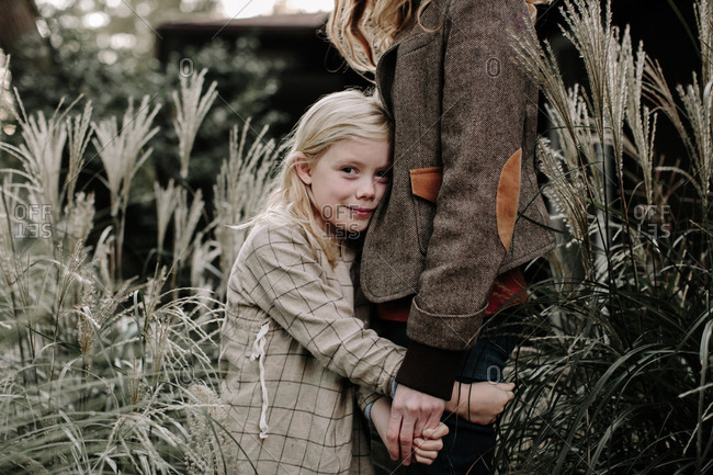 Little girl embracing her mother outdoors