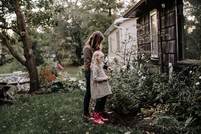 Mother and daughter looking at large plants by house
