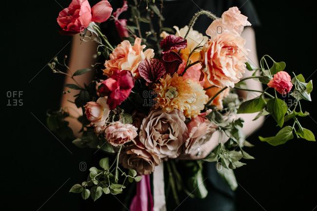 Woman holding large wedding floral arrangement