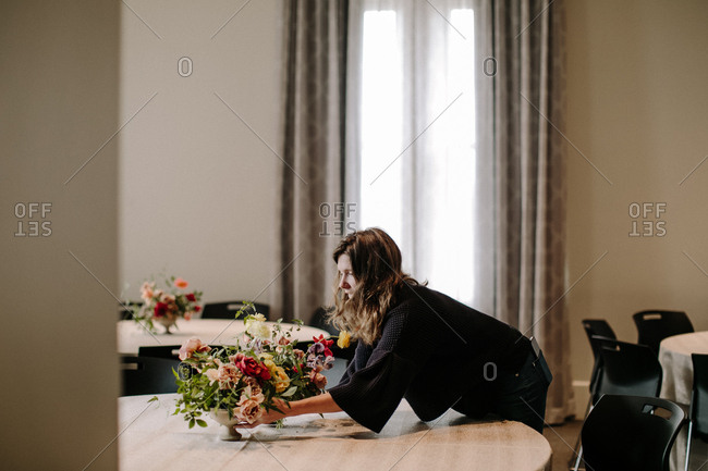 Woman setting wedding floral arrangement on table