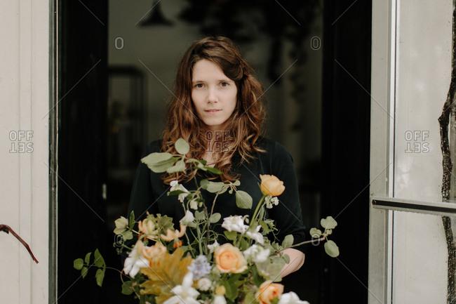 Florist standing by wedding floral arrangement
