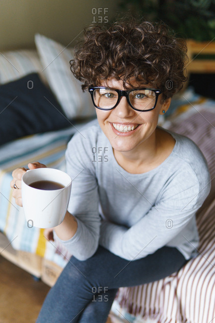 Happy woman with curly hair wearing retro glasses drinking coffee on bed