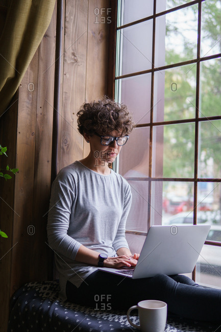 Woman with curly hair wearing retro glasses using laptop