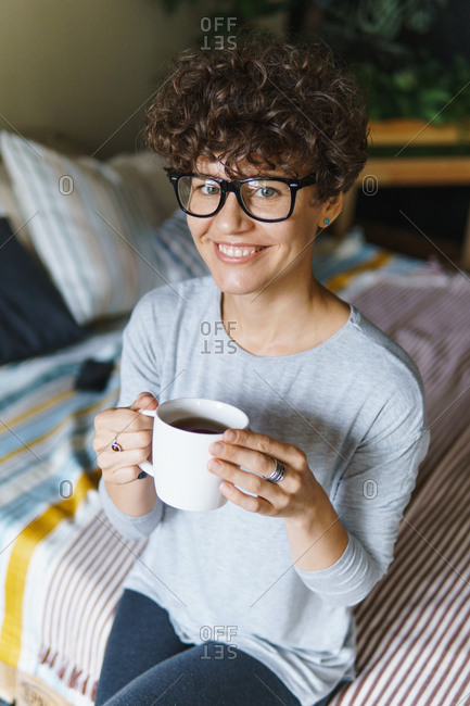 Smiling woman with curly hair wearing retro glasses drinking coffee on bed