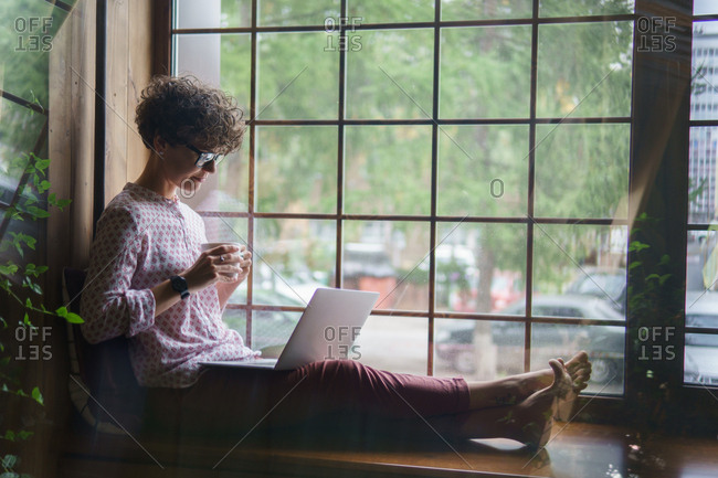 Woman with curly hair sitting by window barefoot using laptop