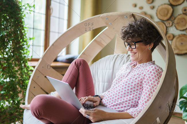 Woman with curly hair laughing while sitting in wooden round chair using laptop