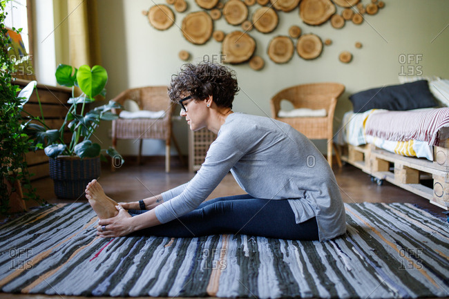 Curly haired woman doing yoga stretches on floor
