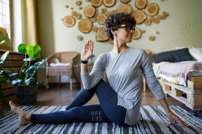 Curly haired woman doing yoga on floor
