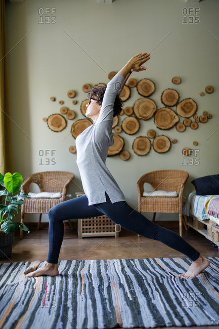 Curly haired woman yoga warrior pose