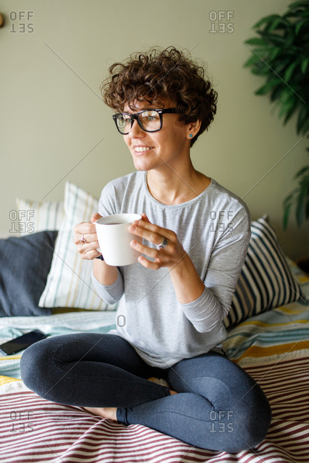 Happy woman wearing retro glasses drinking coffee on bed