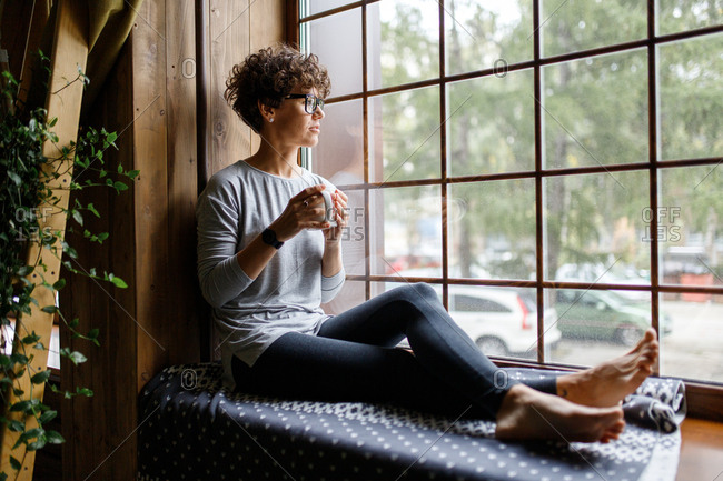 Woman with curly hair drinking coffee by window