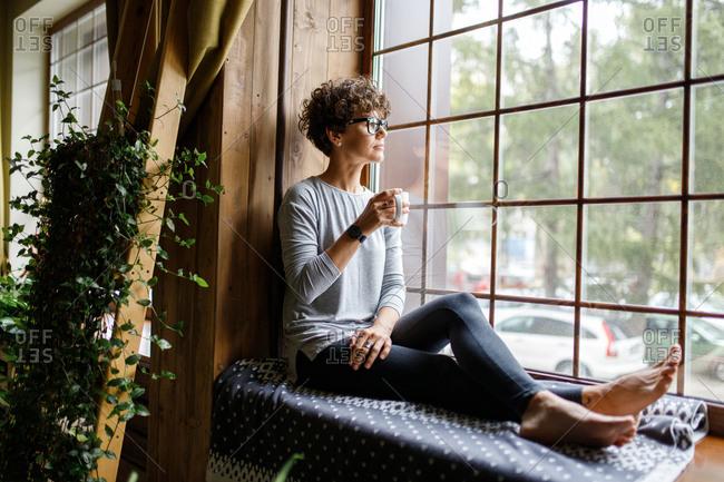 Woman drinking coffee by window