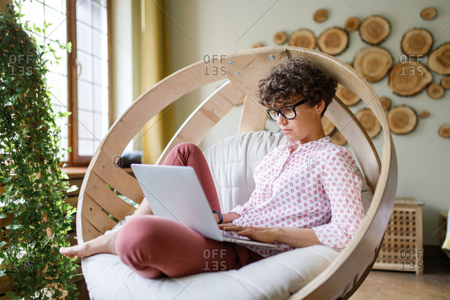 Woman relaxing in round chair using laptop
