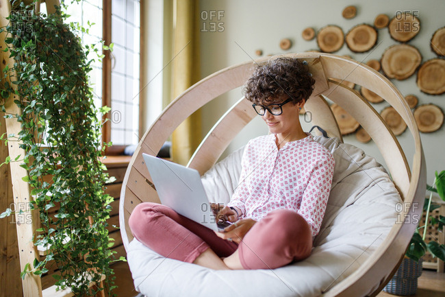 Woman sitting in round chair using laptop