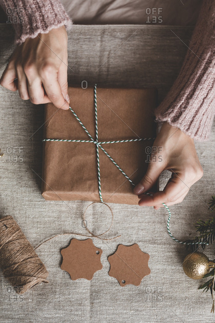 Hands tying twine around a brown paper package