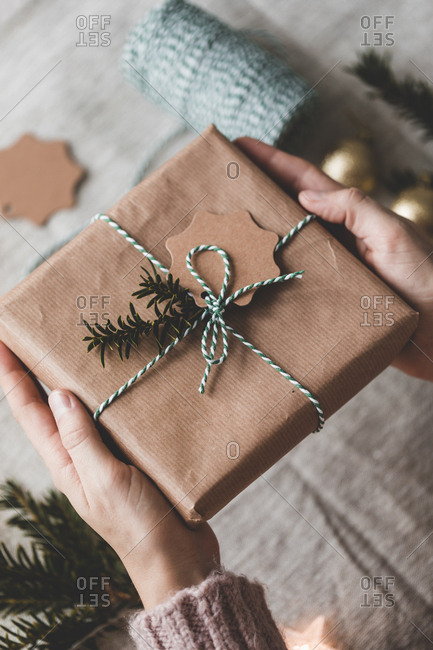Hands holding a wrapped holiday present