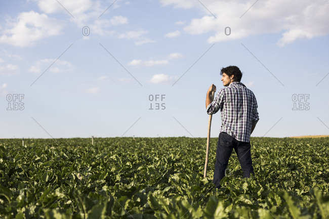 Man in casual outfit looking away standing amidst green plants in beautiful farm field in Salamanca, Spain