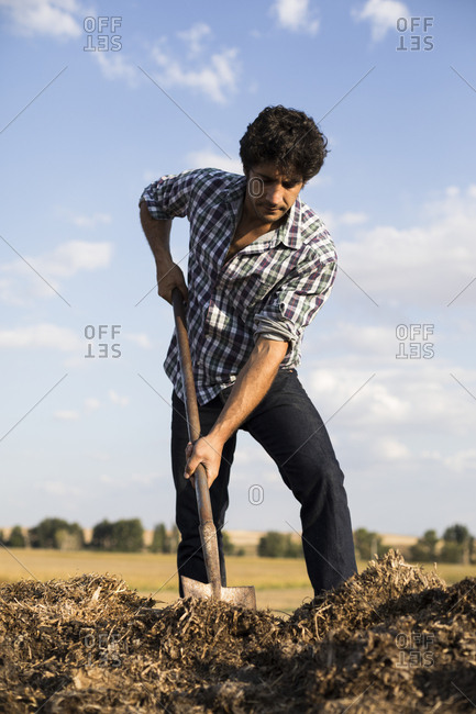Man in casual outfit working with a shovel in a farm in Salamanca, Spain