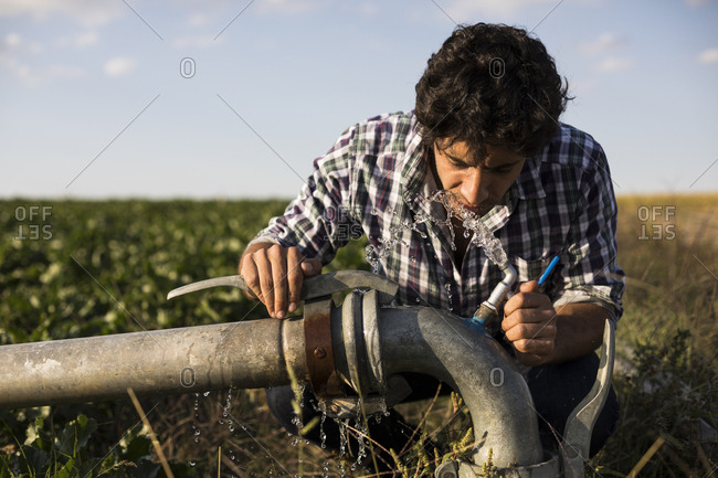 Man in casual outfit drinking from a watering pipe in a farm in Salamanca, Spain