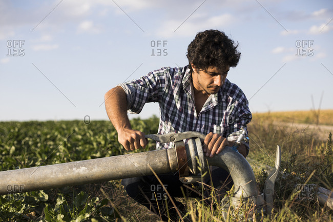 Man in casual outfit examining a watering pipe in a farm in Salamanca, Spain