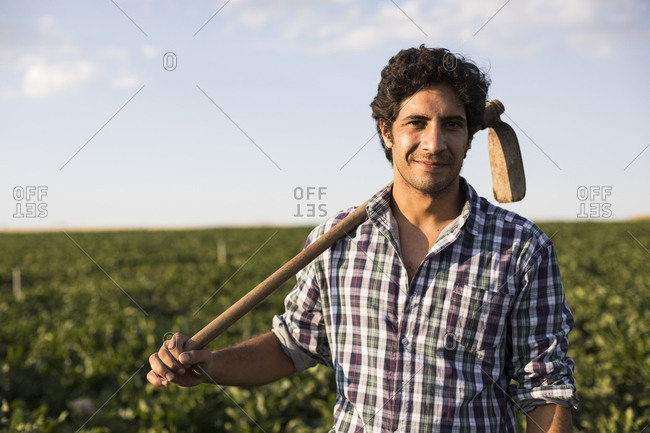 Man in checkered shirt with a hoe looking at camera while standing in a farm field at sunset in Salamanca, Spain