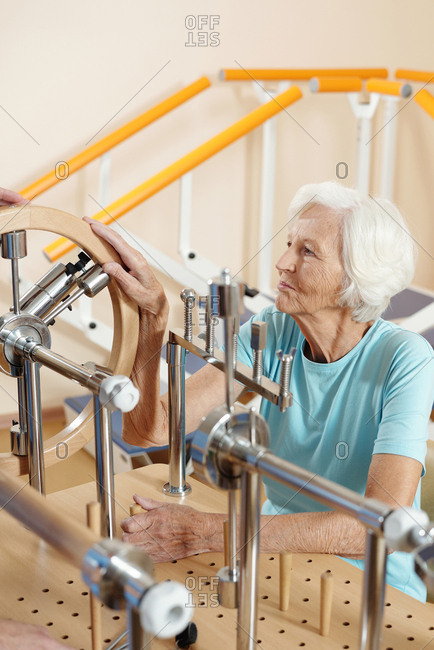 Physical therapy for seniors. Aged Caucasian woman doing exercises on motor training equipment in rehabilitation center for stroke recovery