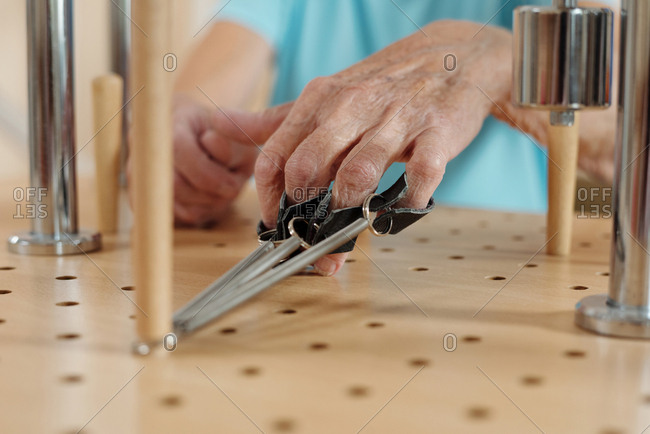 Physical activity on motor skills. Hand of anonymous senior woman doing exercises on training equipment in neurological hospital, close-up view