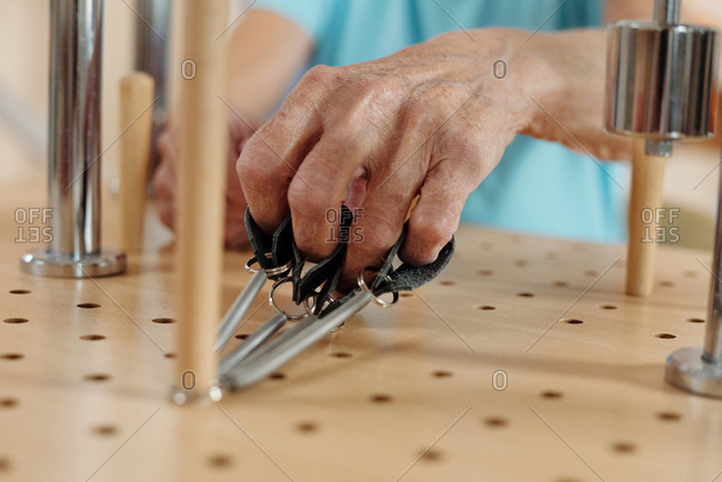 Hand of unrecognizable elderly woman developing motor skills on special physical therapy device in rehabilitation center, close-up view