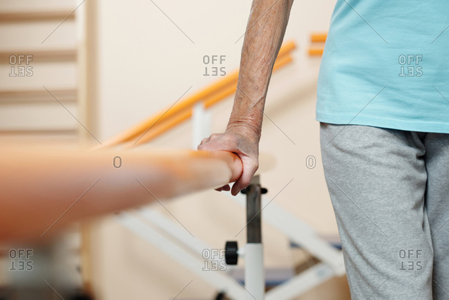 Physiotherapy in rehab center. Close-up view of unrecognizable elderly woman holding to training equipment while learning to walk after surgery