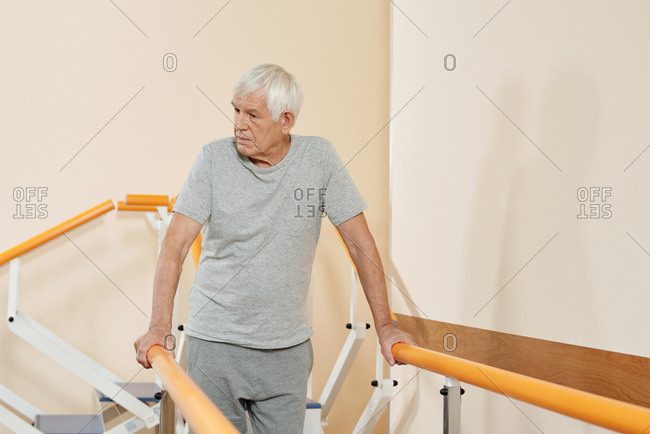 Physical therapy for seniors. Elderly Caucasian man doing first steps with equipment in rehabilitation center after neurological disease
