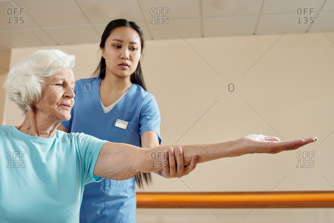 Elderly Caucasian woman doing exercises in rehabilitation center while young Asian female physical therapist helping and controlling her