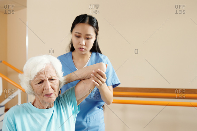 Young Asian female physiotherapist assisting senior Caucasian woman doing physical exercises in recovery center and overcoming pain