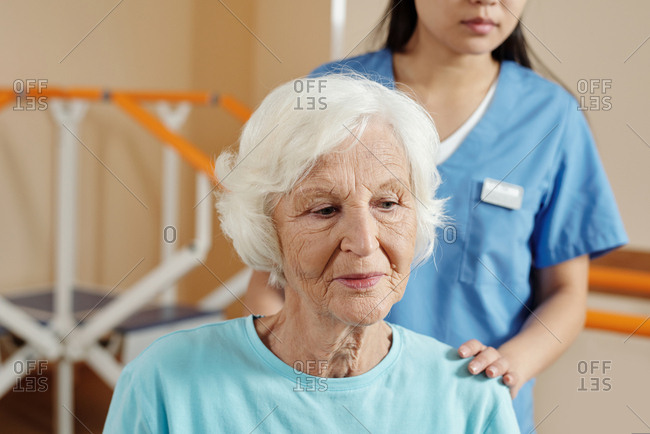 Elderly patient on physical therapy. Portrait of senior Caucasian woman looking down thoughtfully while getting ready for training in rehab hospital