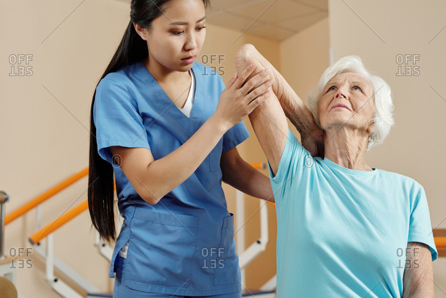 Physical therapy for seniors. Young professional Asian nurse helping elderly Caucasian woman to do physical exercises in rehabilitation hospital
