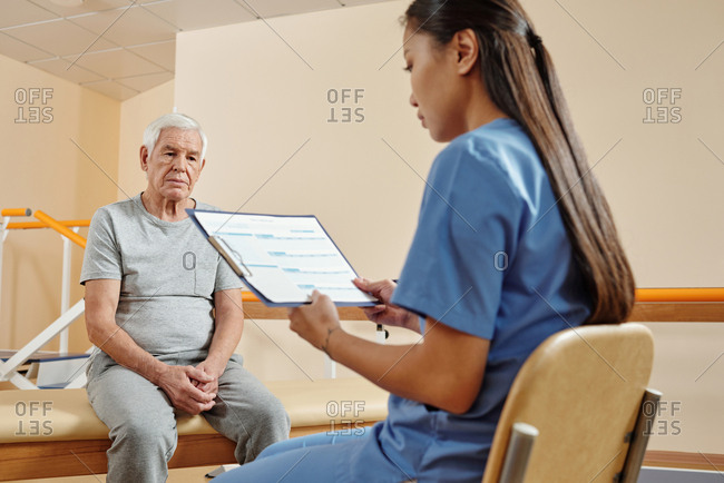 Young professional female physiotherapist looking at medical record of elderly Caucasian male patient sitting on couch in rehab center