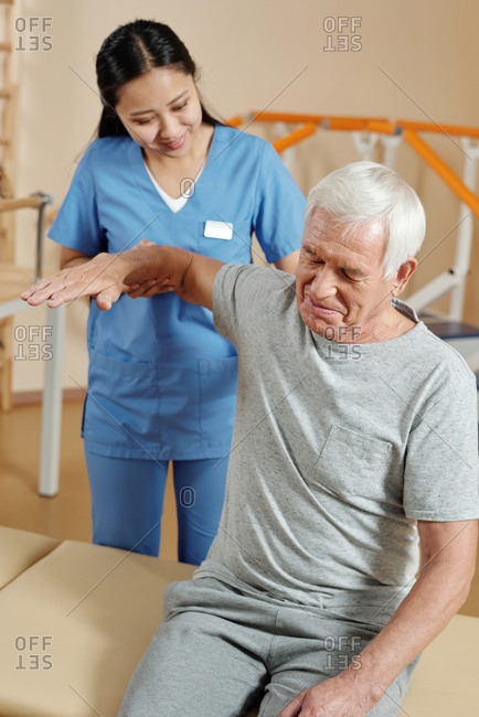 Physical therapist working with patient. Aged Caucasian man smiling while doing physical exercises in recovery center with young caring Asian nurse