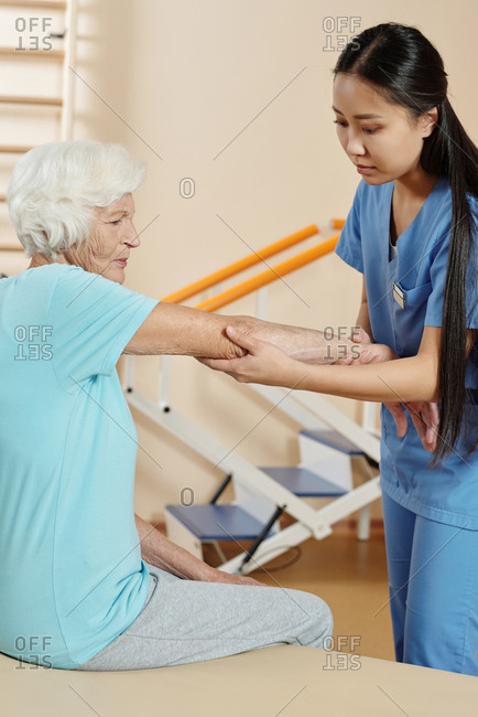 Young female Asian  physical therapist doing checkup of senior Caucasian woman sitting on couch in rehabilitation hospital